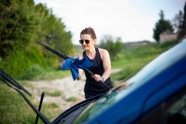 Giovane donna che pulisce un veicolo blu del furgone.