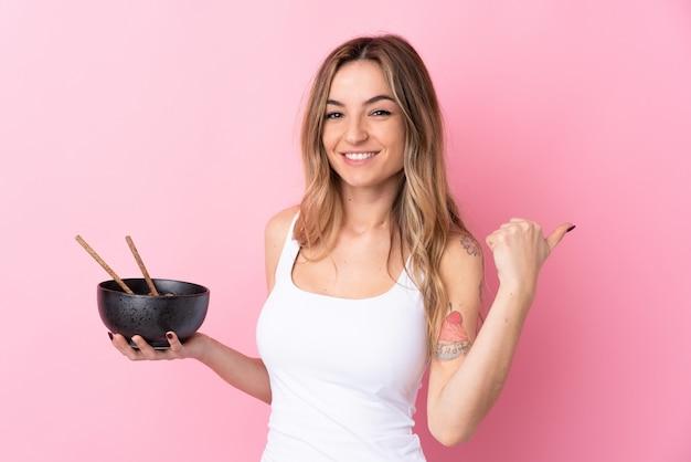Giovane donna che punta al lato per presentare un prodotto mentre si tiene una ciotola di noodles con le bacchette