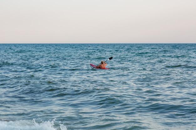 Giovane donna che rema il kajak del mare. vacanza attiva.