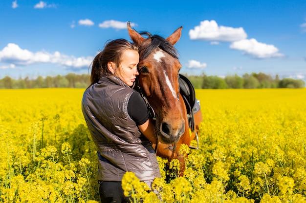 Giovane donna che resta vicino al cavallo marrone nel campo giallo della colza o del colza con cielo blu