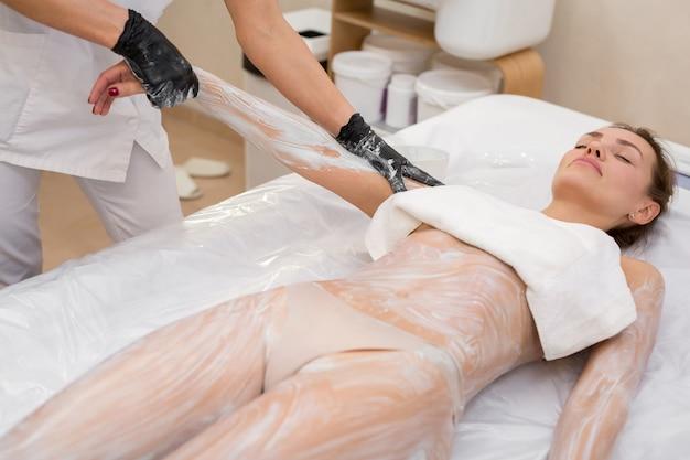 Giovane donna che riceve argilla cosmetica, maschera corpo alghe marine sdraiato sul lettino da massaggio al salone di bellezza. il cosmetologo del primo piano applica una maschera idratante sulla mano di una giovane donna.