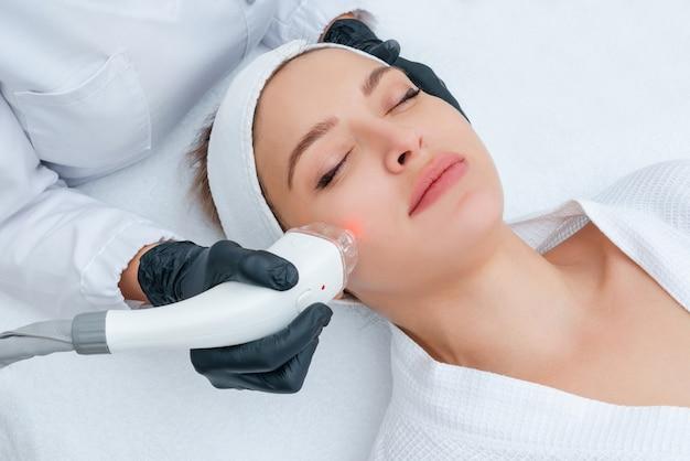 Giovane donna che riceve il trattamento laser nella clinica di cosmetologia