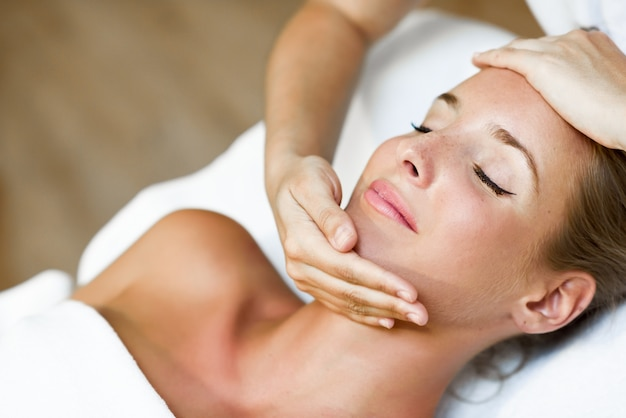 Giovane donna che riceve un massaggio alla testa in un centro termale.
