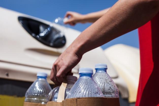 Giovane donna che ricicla le bottiglie di plastica