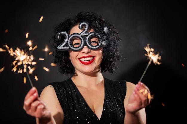 Giovane donna che ride con le stelle filanti. bruna con i capelli ricci. festa di capodanno.