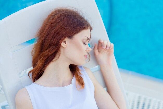 Giovane donna che riposa in piscina.
