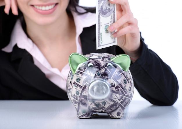 Giovane donna che risparmia soldi in un porcellino salvadanaio.