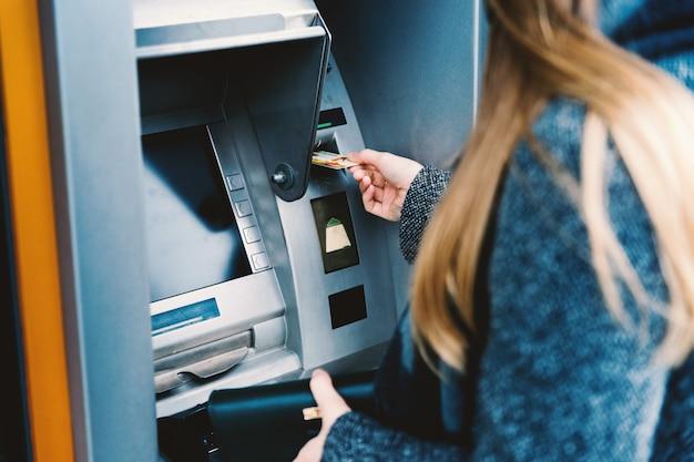 Giovane donna che ritira i soldi dalla carta di credito al bancomat