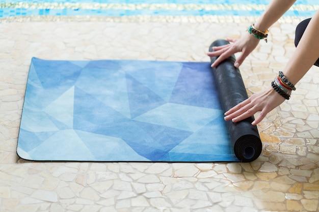 Giovane donna che rotola la sua stuoia blu di yoga dopo una lezione di yoga sul pavimento vicino ad uno stagno
