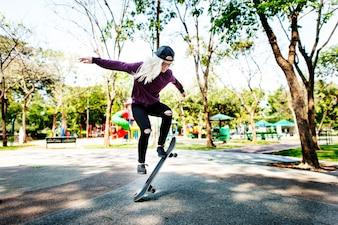 Giovane donna che salta il concetto di Olly Skateboard
