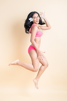 Giovane donna che salta in costume da bagno