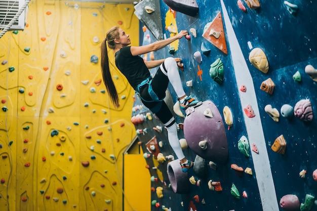 Giovane donna che scala una parete di roccia alta, indoor, artificiale