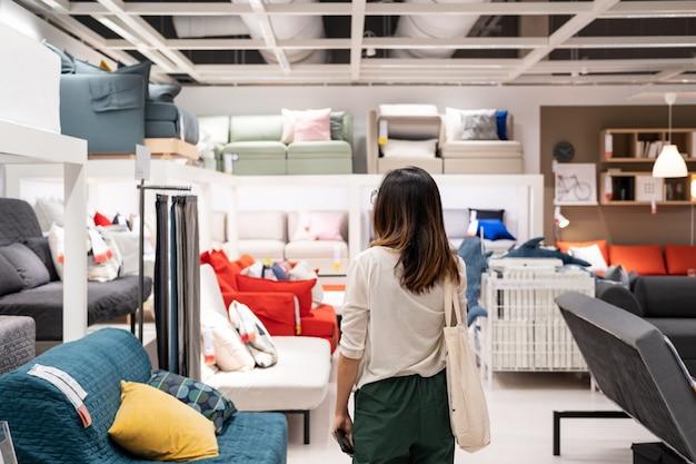 Giovane donna che sceglie mobili in un negozio di arredamento di casa moderna