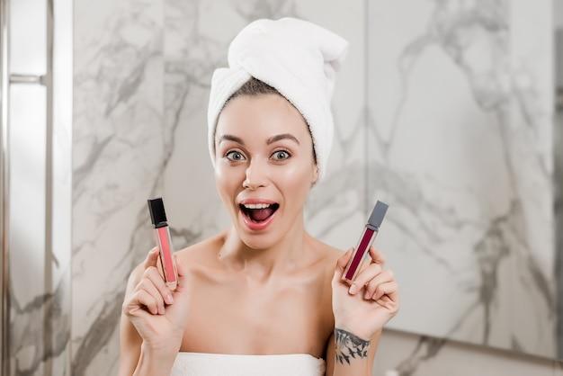 Giovane donna che sceglie rossetto con un sorriso avvolto in asciugamani in bagno
