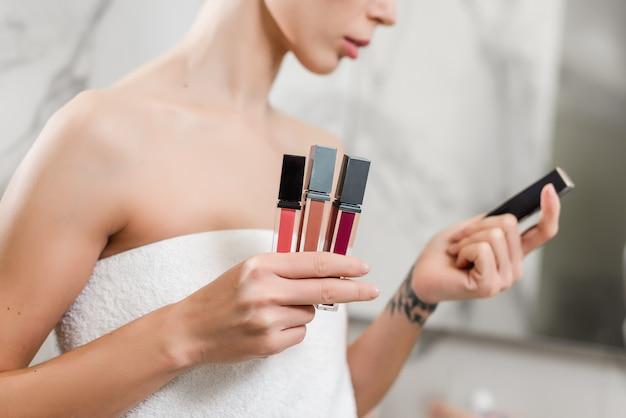 Giovane donna che sceglie rossetto da vari colori avvolti in asciugamani in bagno
