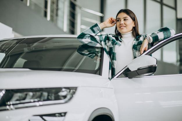 Giovane donna che sceglie un'automobile in una sala d'esposizione dell'automobile