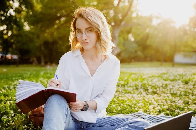 Giovane donna che scrive qualcosa sul taccuino nel parco