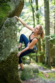 Giovane donna che si arrampica sui grandi massi all'aperto giorno d'estate