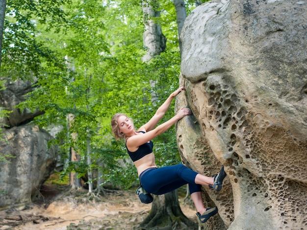 Giovane donna che si arrampica sui grandi massi all'aperto