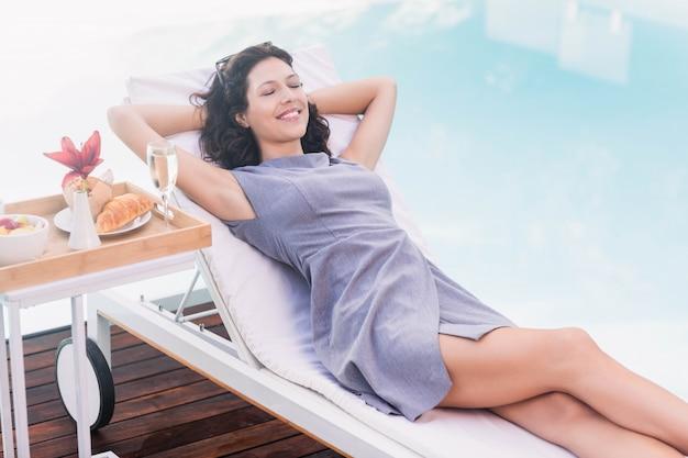Giovane donna che si distende su un lettino vicino al bordo piscina
