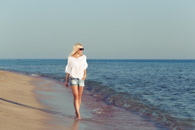 Giovane donna che si distende sulla spiaggia