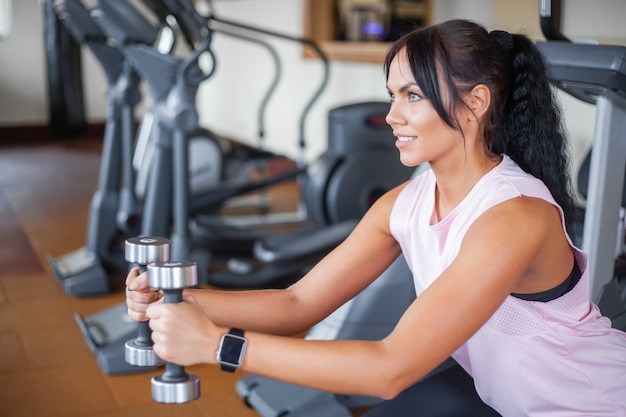 Giovane donna che si esercita con il peso in palestra