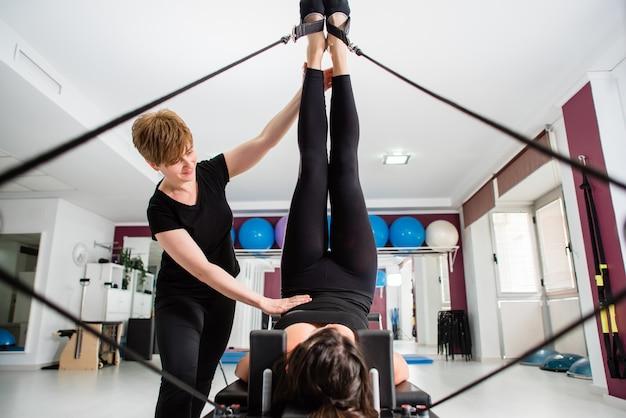 Giovane donna che si esercita sul riformatore del dispositivo pilates con istruttore in palestra