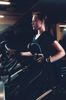 Giovane donna che si esercita sulla macchina cardio ellittica