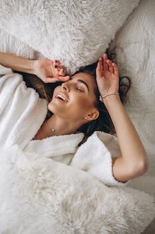 Giovane donna che si estende nel letto
