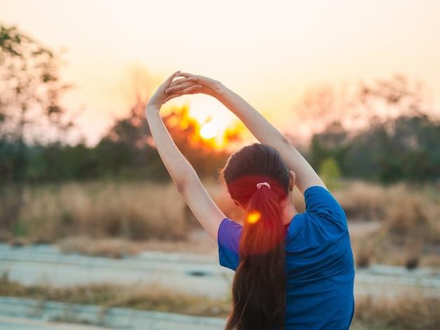 Giovane donna che si estende prima di correre. ragazza sportiva che si prepara a correre nel parco.