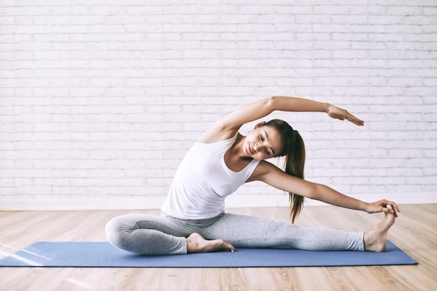 Giovane donna che si estende sul pavimento come trapano mattutino per sviluppare flessibilità