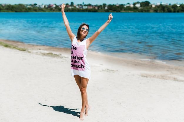 Giovane donna che si estende sulla spiaggia