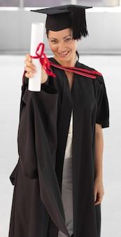 Giovane donna che si laurea tenendo il suo diploma