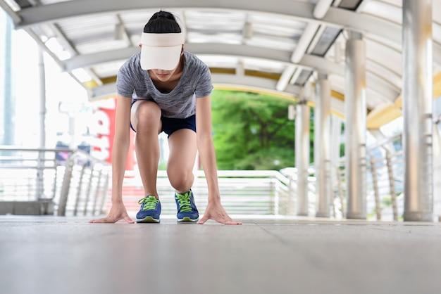 Giovane donna che si prepara a correre in città.