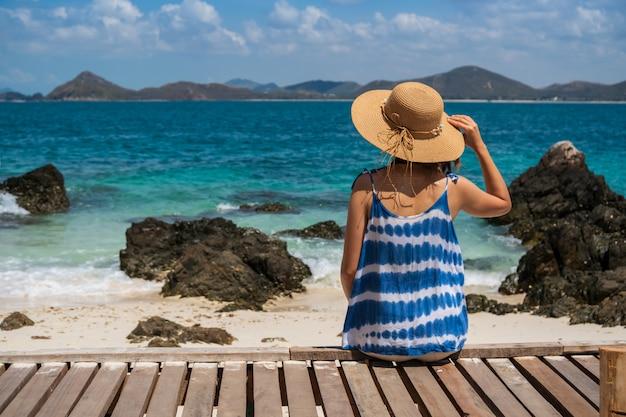 Giovane donna che si rilassa e che gode al concetto tropicale della spiaggia, di vacanze estive e di viaggio
