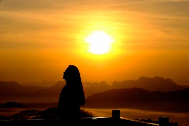 Giovane donna che si rilassa nello stile all'aperto di libertà della ragazza della gente del cielo di alba o di tramonto dell'estate sul fondo della collina della montagna - crepuscolo della donna della siluetta