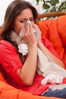 Giovane donna che si siede a casa con il freddo