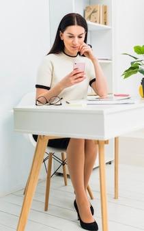 Giovane donna che si siede al tavolo con lo smartphone