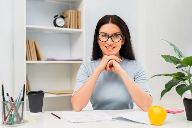 Giovane donna che si siede al tavolo in ufficio