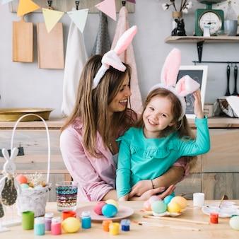 Giovane donna che si siede con la figlia nelle orecchie del coniglietto vicino alle uova di pasqua