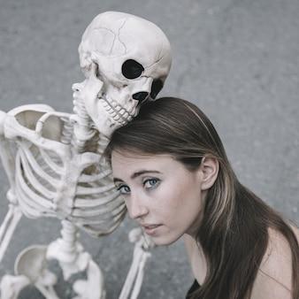 Giovane donna che si siede con lo scheletro e che guarda l'obbiettivo