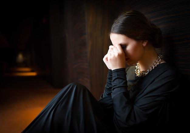 Giovane donna che si siede da solo sulla terra
