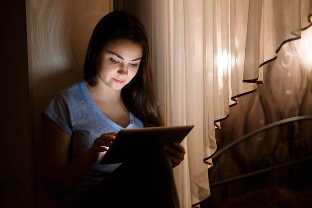 Giovane donna che si siede dalla finestra e che per mezzo della compressa digitale a noioso
