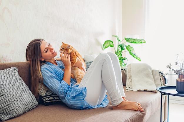 Giovane donna che si siede e che si distende sullo strato in salone e che abbraccia, giocando con l'animale domestico
