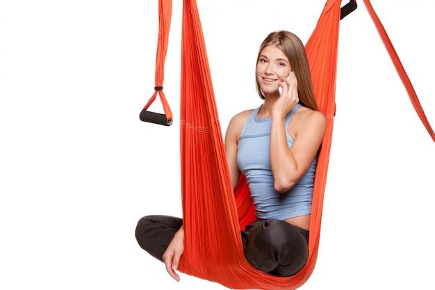 Giovane donna che si siede in amaca per yoga aerea antigravità