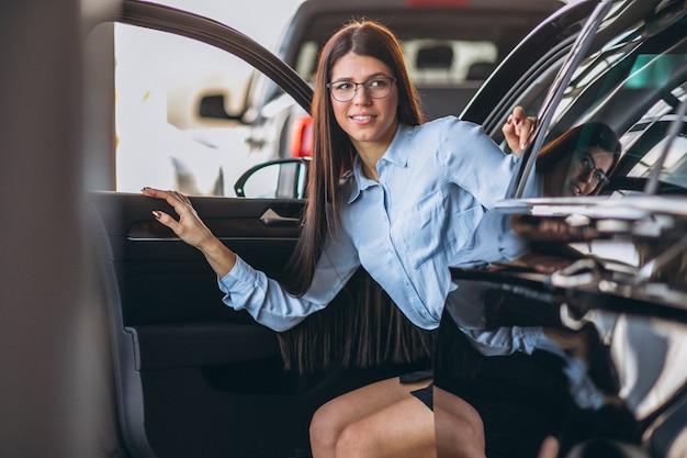 Giovane donna che si siede in macchina