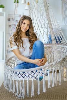Giovane donna che si siede in un'amaca lavorata a maglia