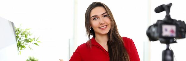 Giovane donna che si siede nell'ufficio di fronte alla macchina fotografica sul treppiede