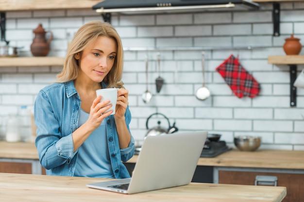 Giovane donna che si siede nella cucina che tiene tazza di caffè guardando portatile