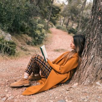 Giovane donna che si siede sotto l'albero sulla strada lettura libro